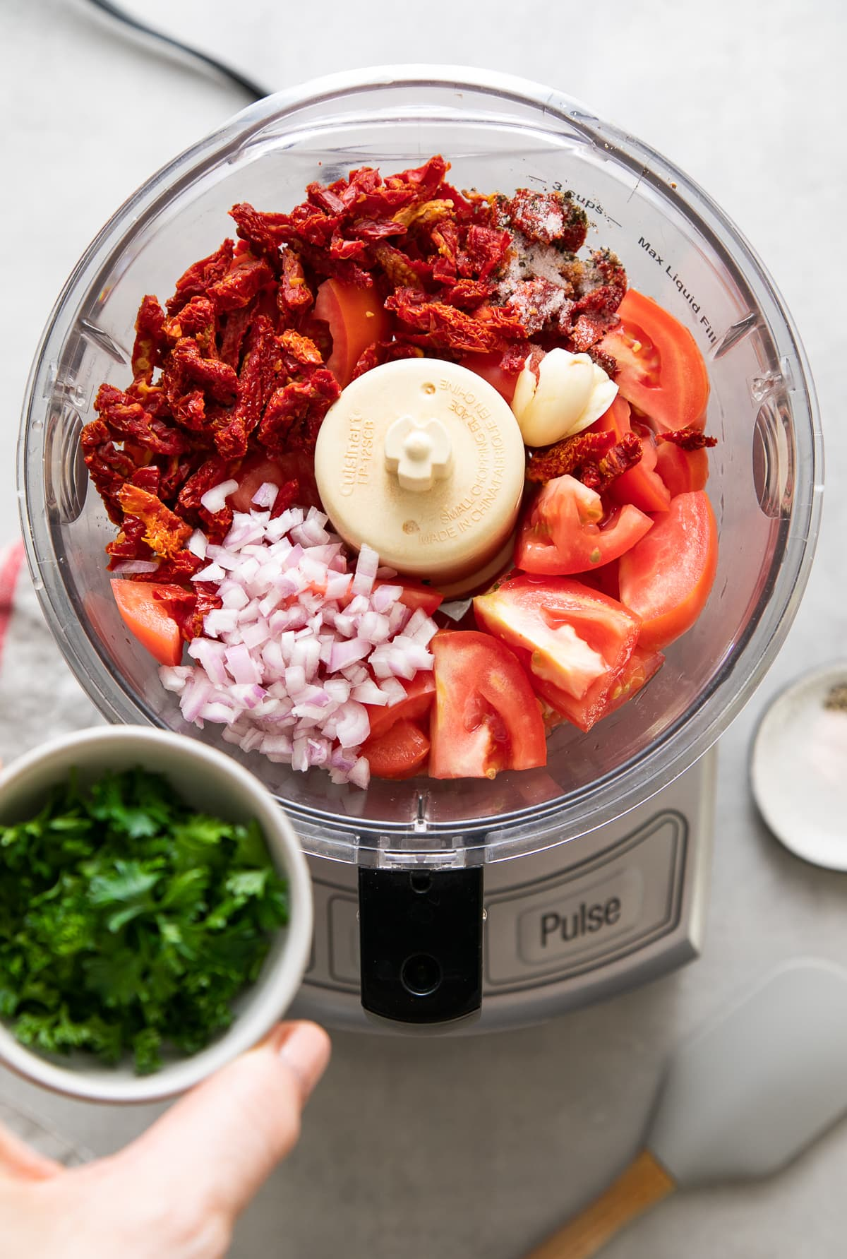 top down view of ingredients for raw marinara sauce added to food processor.