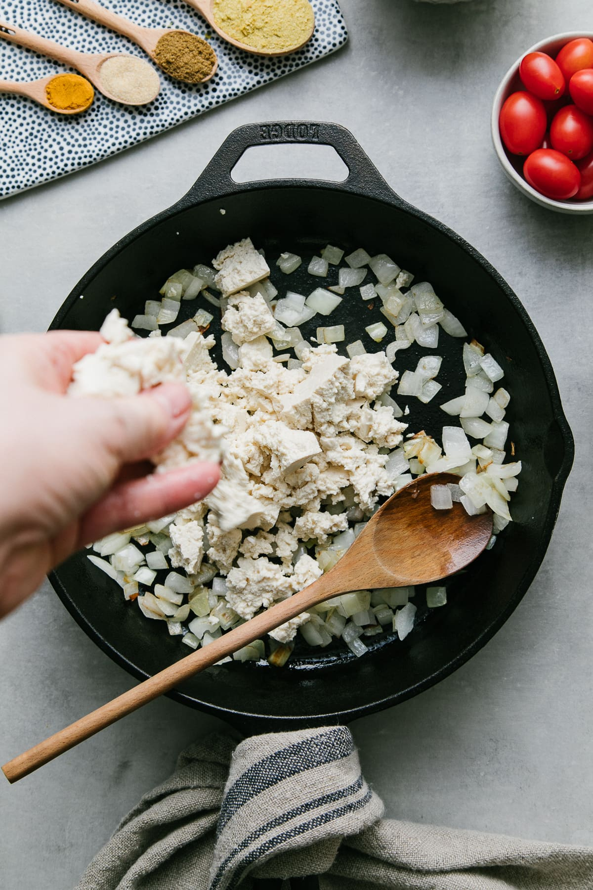 top down view of tofu being crumbled between fingers while adding it to a skillet with onions.