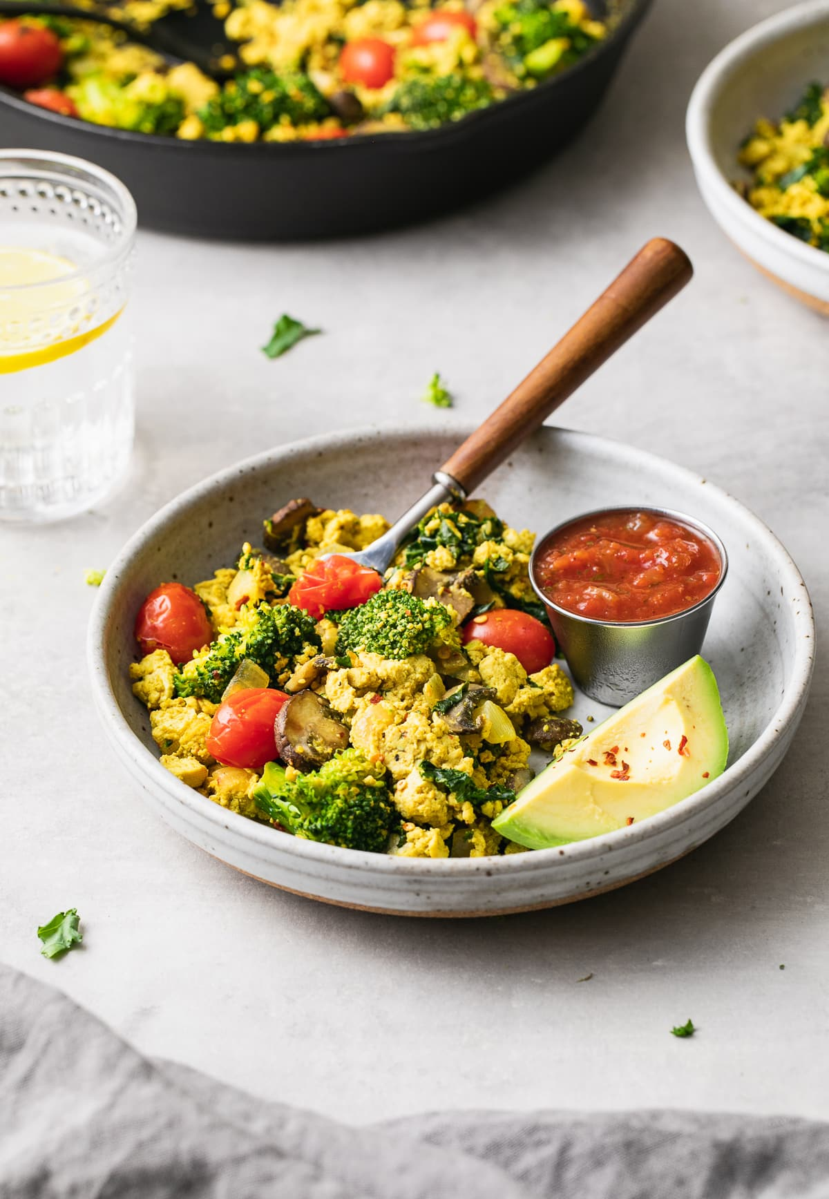 side angle view of a bowl with a serving of southwest tofu scramble with items surrounding.