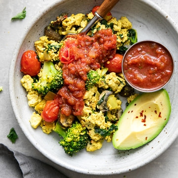 top down view of a bowl with a serving of southwest tofu scramble with items surrounding.