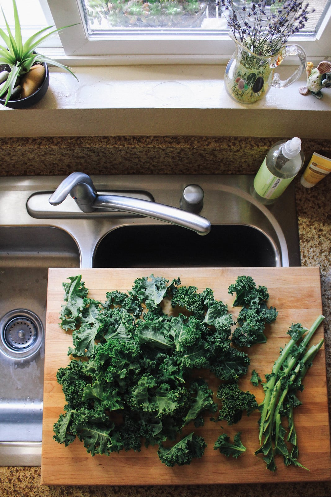 top down view of kale being prepped on a wooden cutting board.