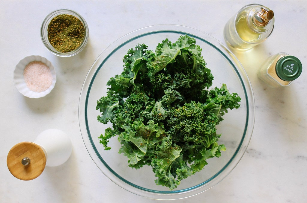 top down view showing the process of making crispy baked kale chips.