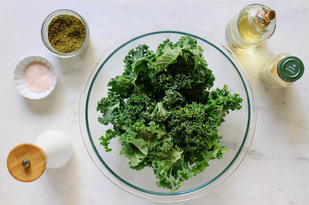 showing how to mix the kale with oil and spices for baked kale chips