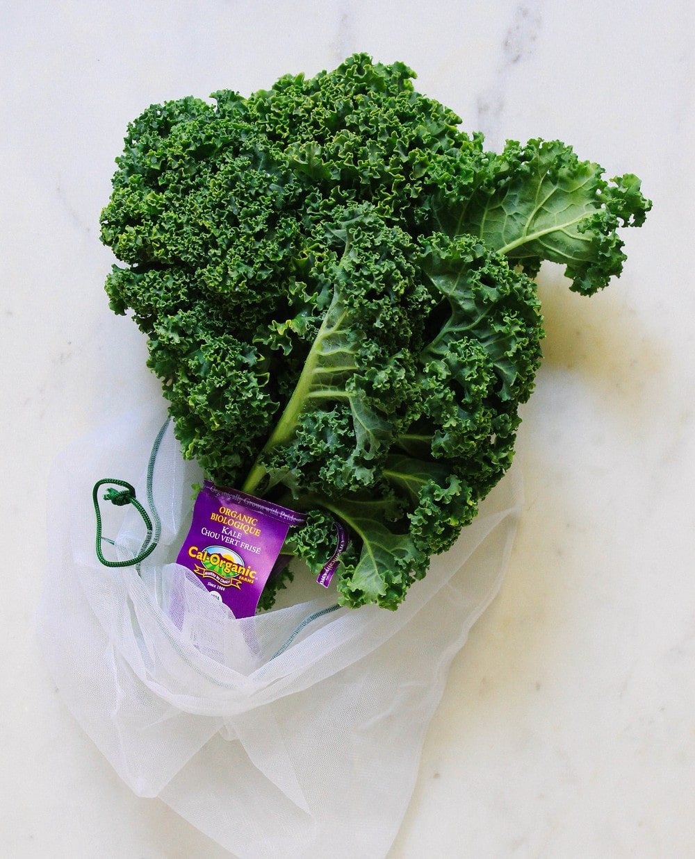 curly kale sticking out of a produce bag