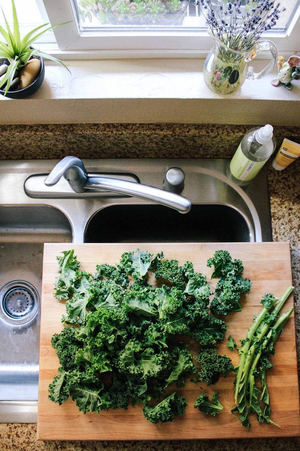 kale on cutting board over sink with stems removed