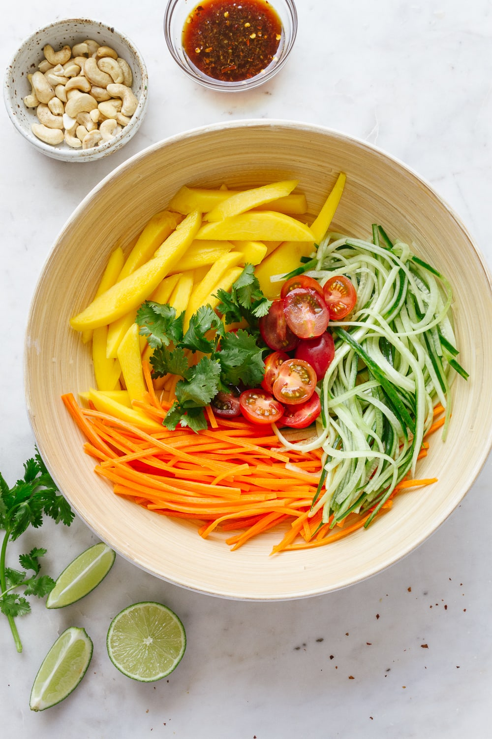 top down view of a bamboo bowl with ingredients of thai mango salad surrounded by cilantro, cashews and dressing in a small glass bowl