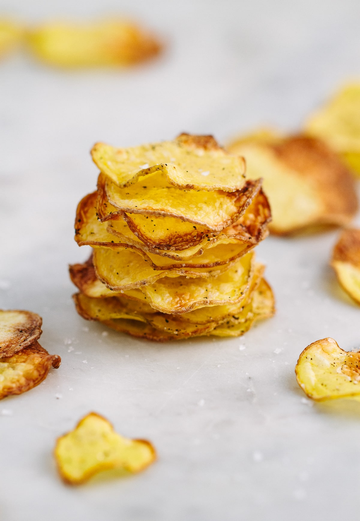 head on view of homemade baked potato chips stacked on top of each other.