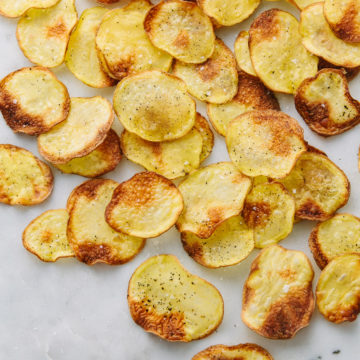 top down view of baked potato chips scattered on a marble slab.
