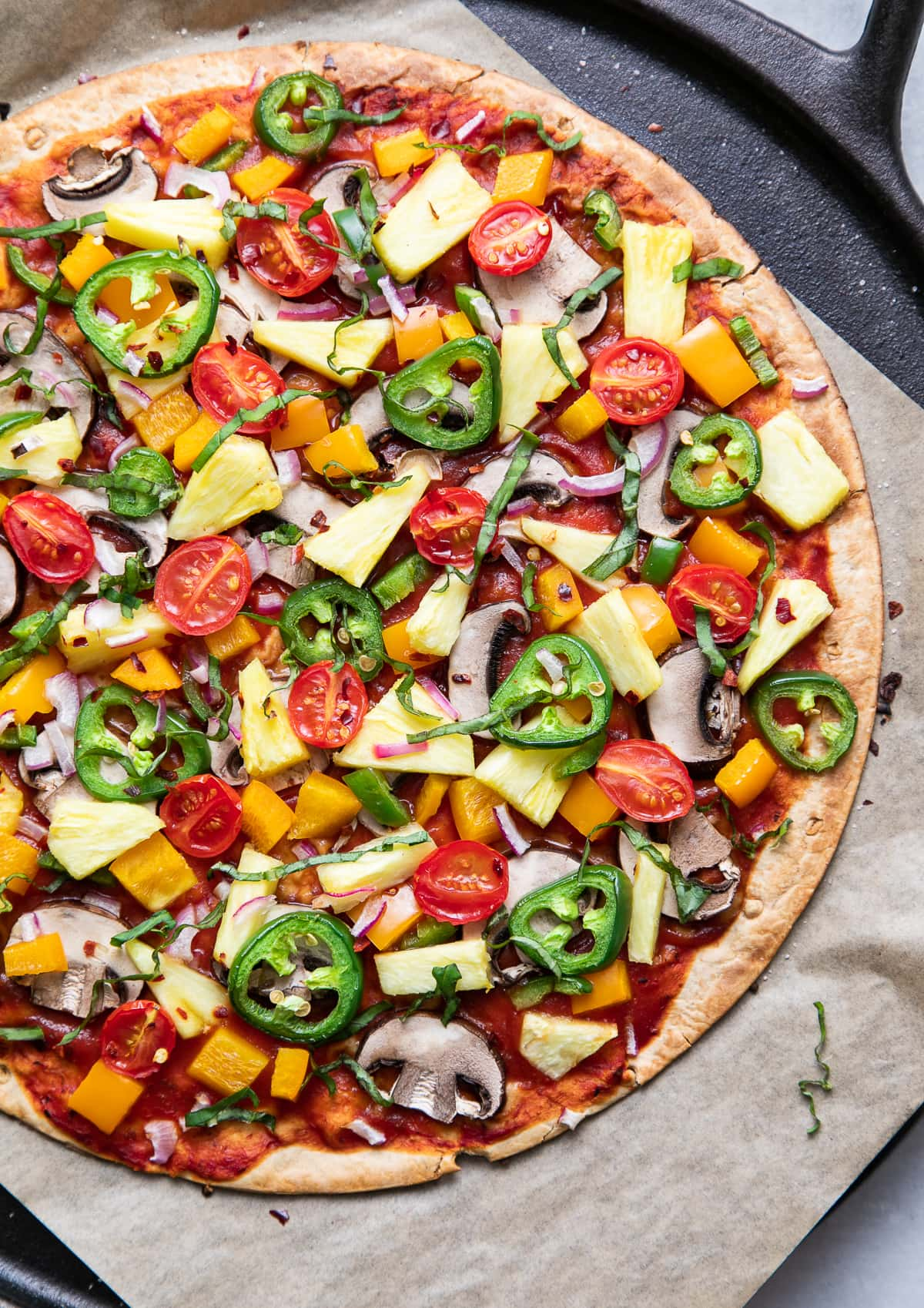 top down view of freshly baked pineapple veggie lovers pizza on a cast iron pizza pan.