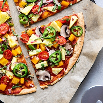 top down view of freshly baked pineapple veggie lovers pizza on a cast iron pizza pan sliced.