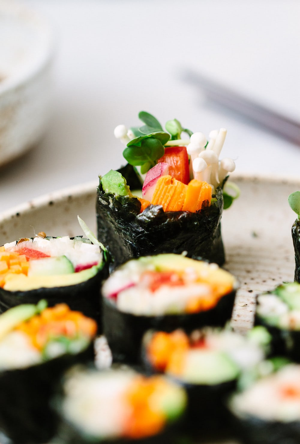 side angle view of sliced vegan sushi roll on a plate