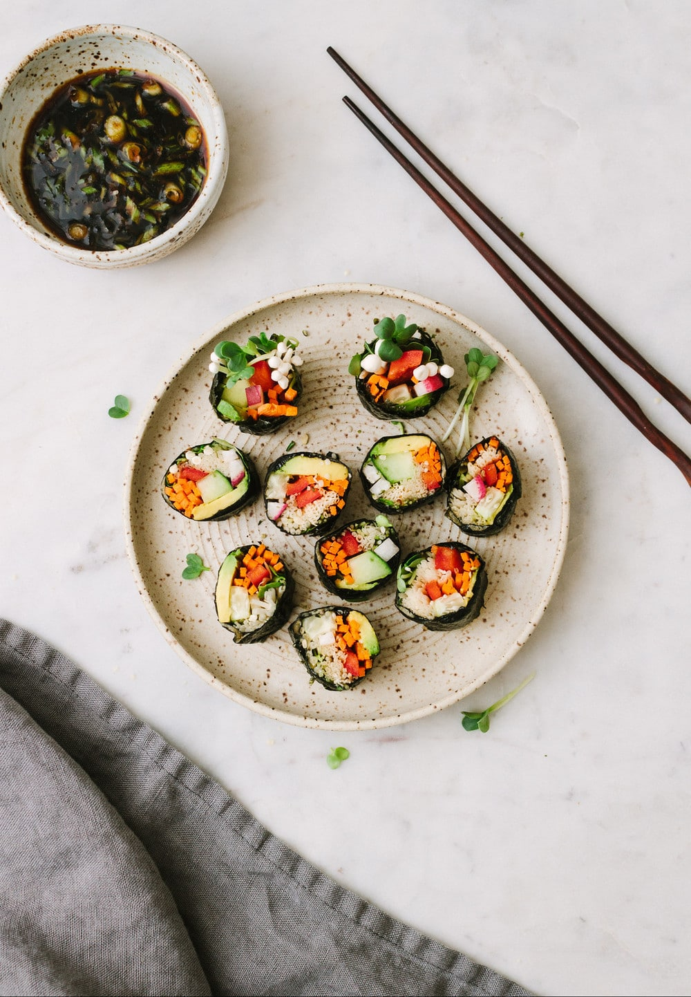 top down view of sushi roll cut up and placed on a small plate with bowl of dipping sauce, chopsticks and grey napkin