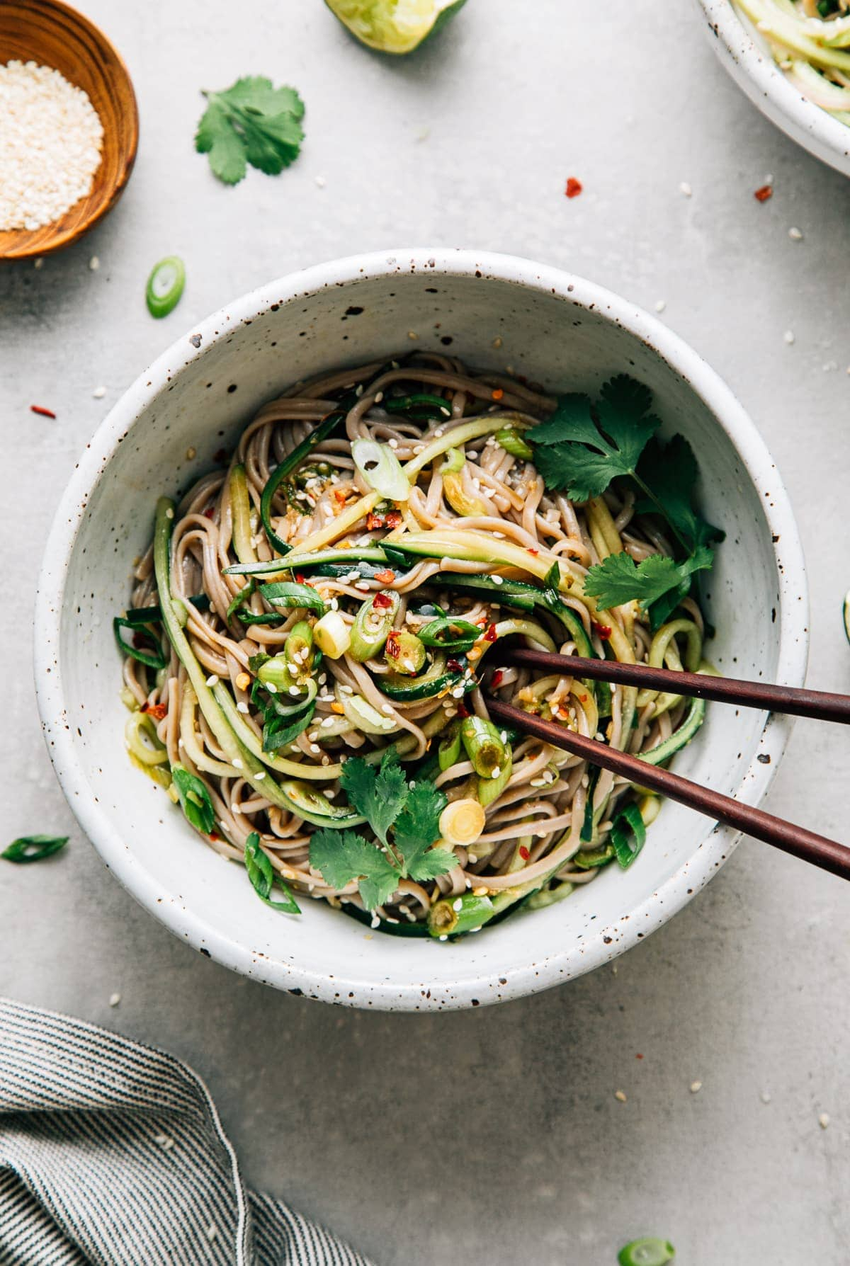 top down view of bowl with serving of soba noodle bowl with cucumber and sesame-ginger scallion sauce with chopsticks.