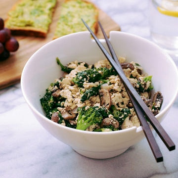 tofu scramble with mushrooms and broccoli in white bowl with wooden chop sticks