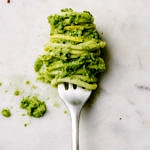zucchini pesto and noodles wrapped around a fork on a marble slab
