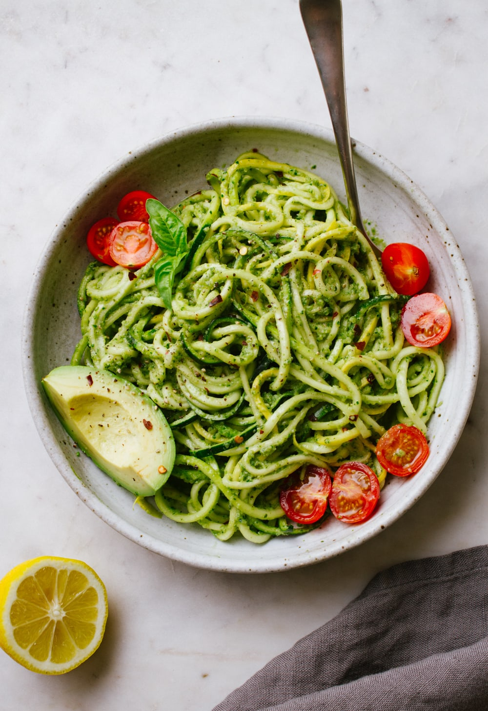 top down view of zucchini noodles with vegan zucchini pesto in a bowl with cherry tomatoes and avocado