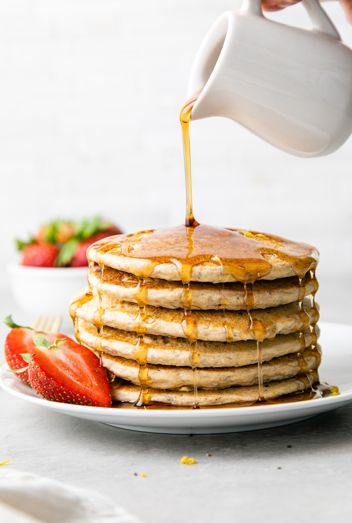 head on view of maple syrup being poured on lemon chia seed pancakes stacked on a small plate.