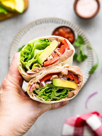 top down view of hand holding refried bean avocado lavash wrap sliced in half.