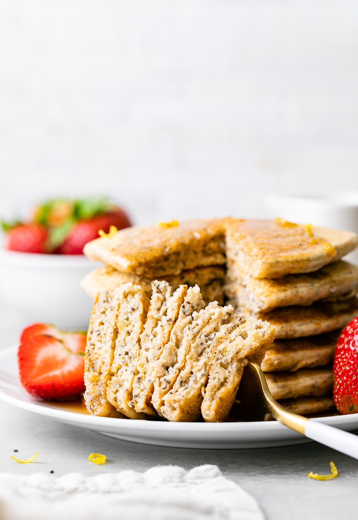 head on view of stack of lemon chia seed pancakes with sliced removed on a fork.