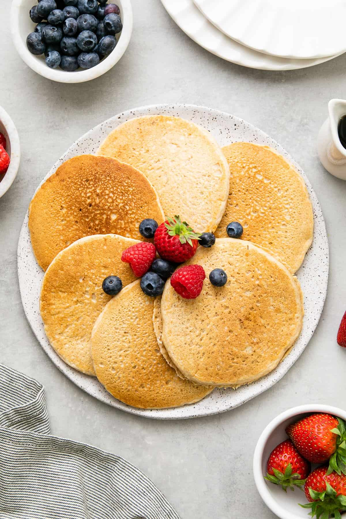 top down view of the best classic vegan pancakes on a serving dish with items surrounding.