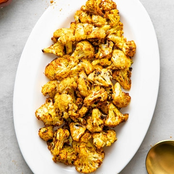 top down view of a serving platter with freshly made curry sriracha roasted cauliflower.