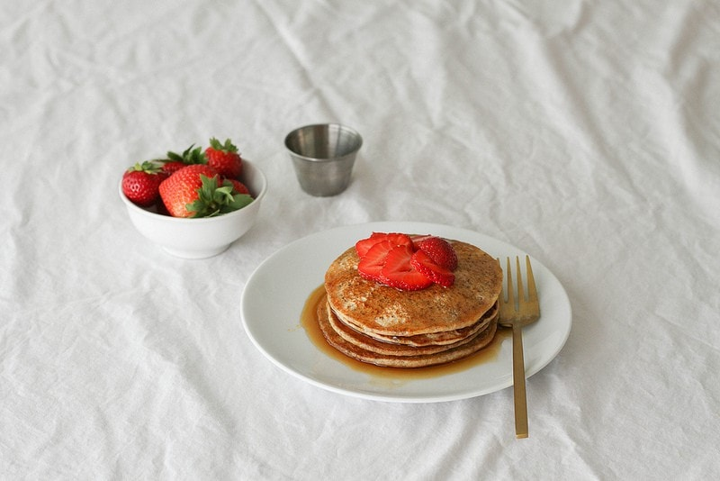 lemon chia seed pancakes on a white plate with strawberries and maple syrup