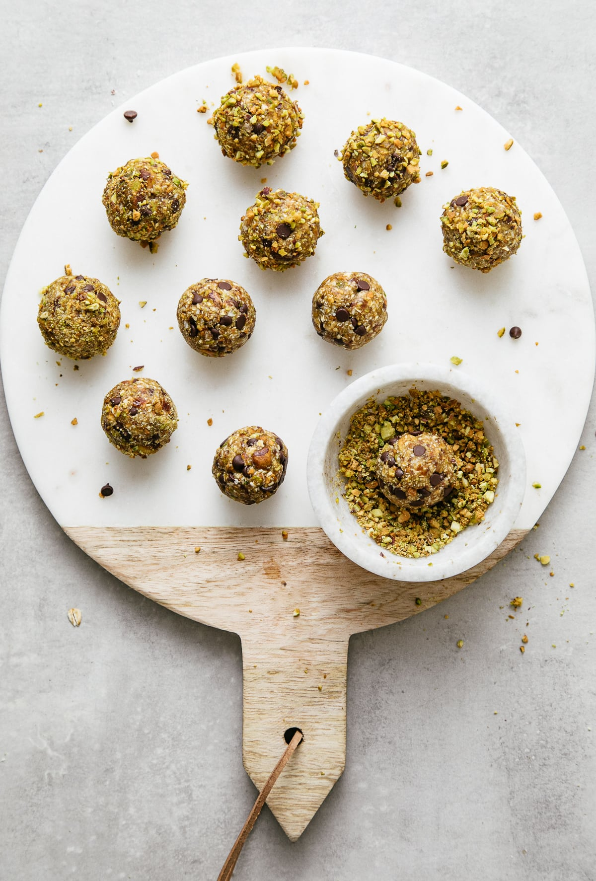 top down view showing rolling no bake cookie balls in crushed pistachios.