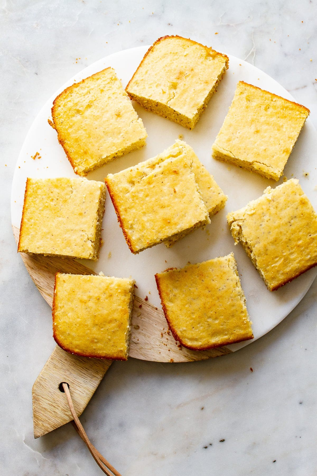 top down view of a group of cornbread slices on a marble serving tray.