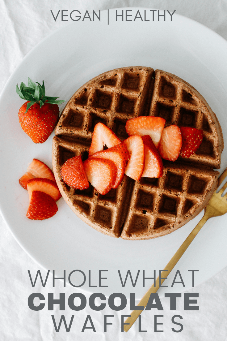 vegan whole wheat chocolate waffles on a white plate with fresh sliced strawberries
