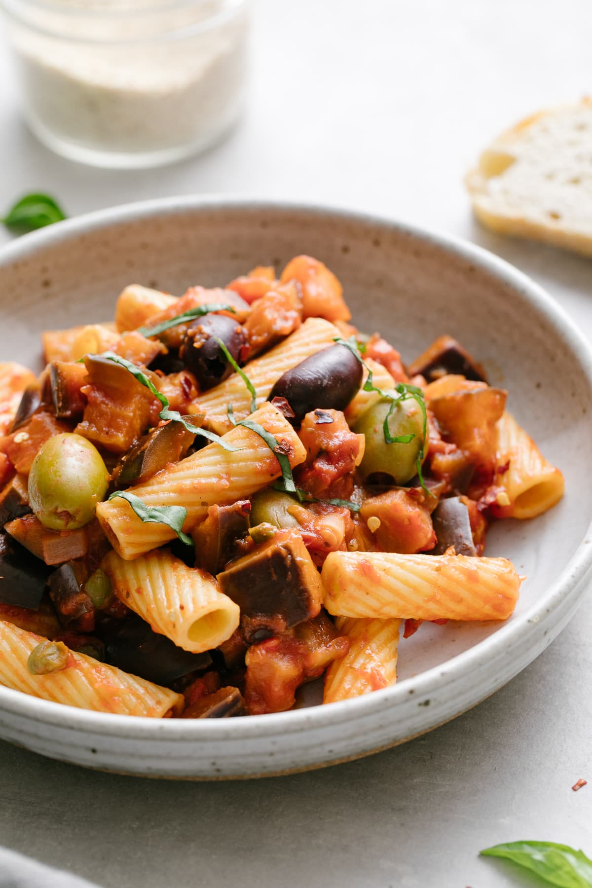 side angle view of a serving of eggplant puttanesca with pasta in a bowl with items surrounding.