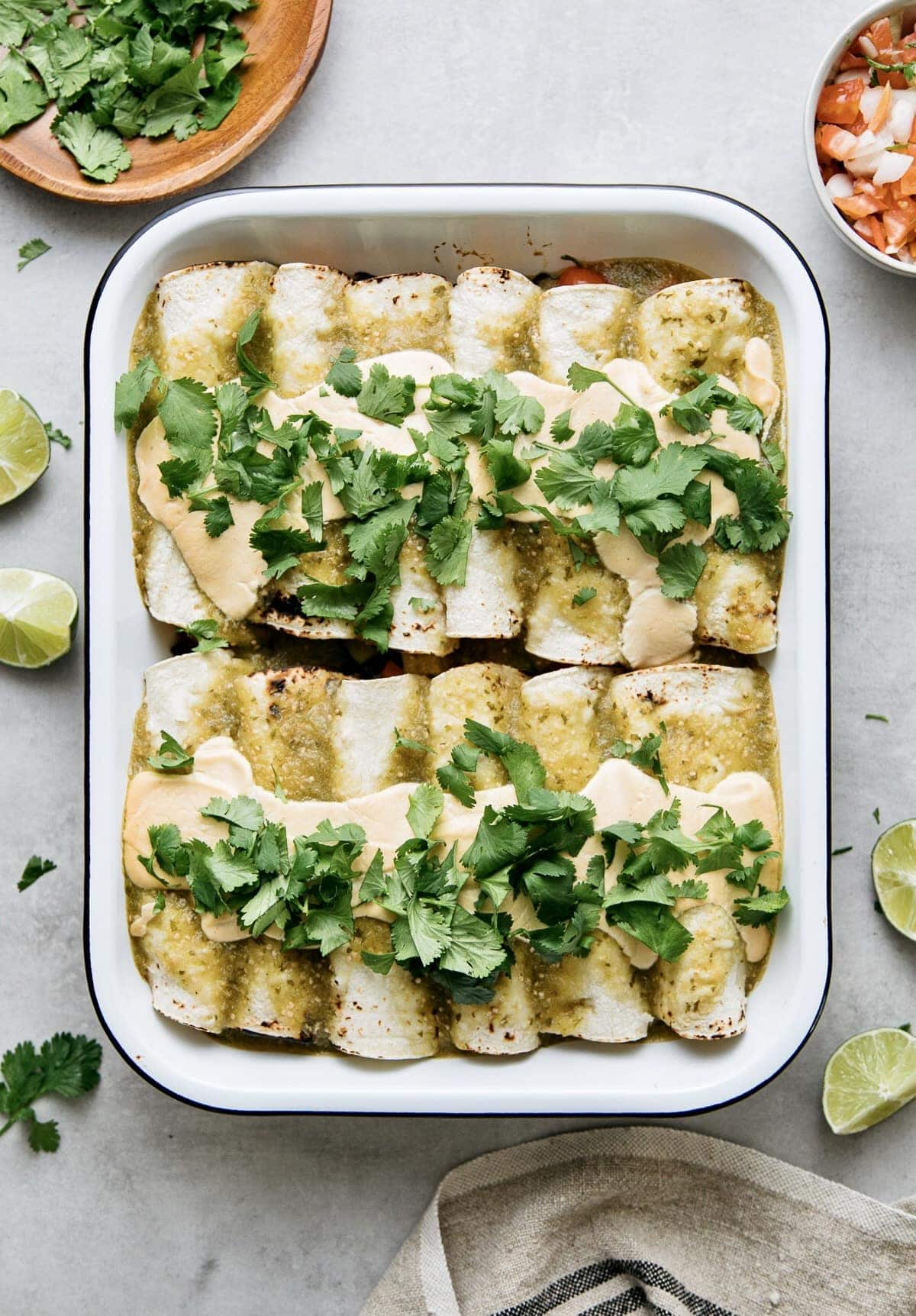 top down view of baking dish with homemade vegan enchiladas verde with items surrounding.
