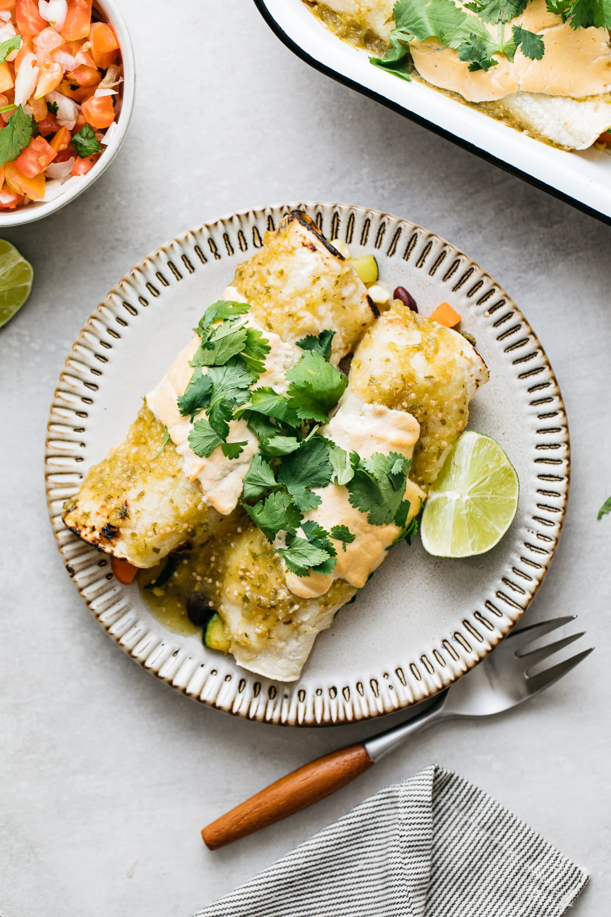 top down view of vegan enchilada verde on a small plate with items surroundings.