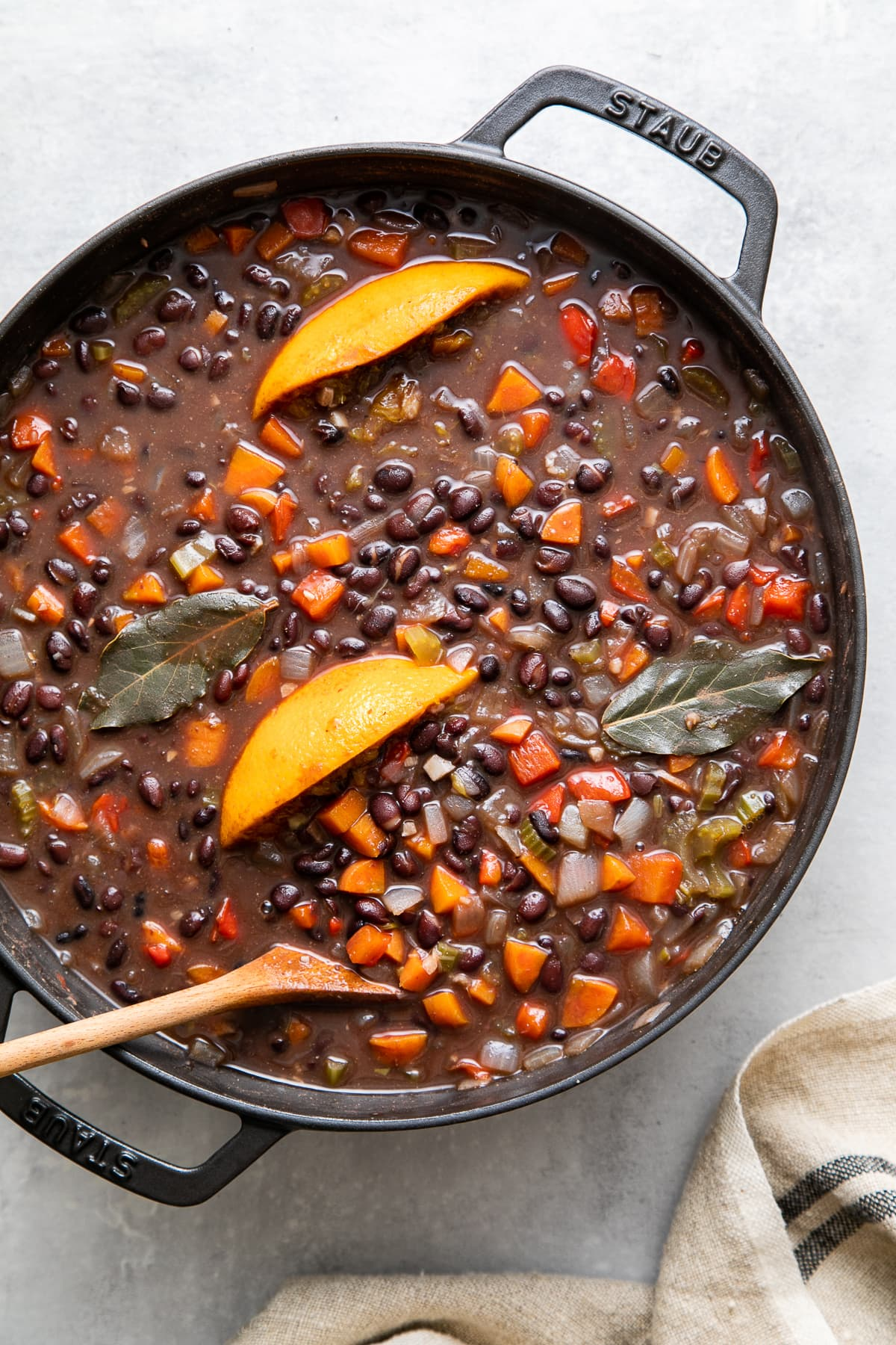 top down view of freshly made pot of cuban black bean soup in a black pot before pureeing.