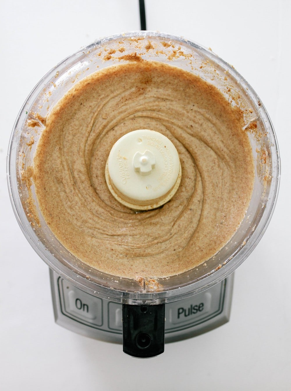 top down view of homemade almond butter finished processing in a food processor, result is smooth creamy almond butter