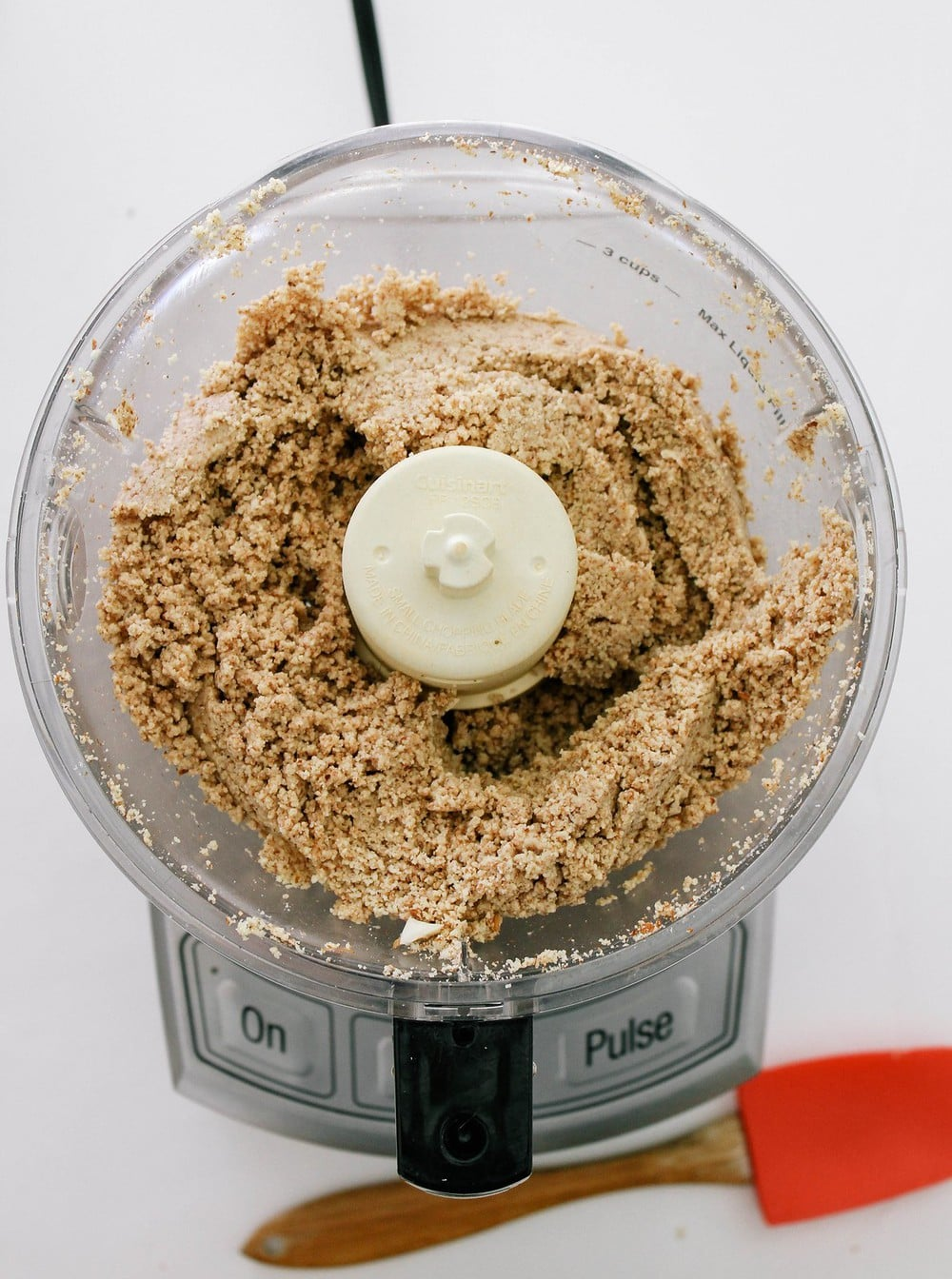 top down view of almond butter processing in food processor for about 5 minutes