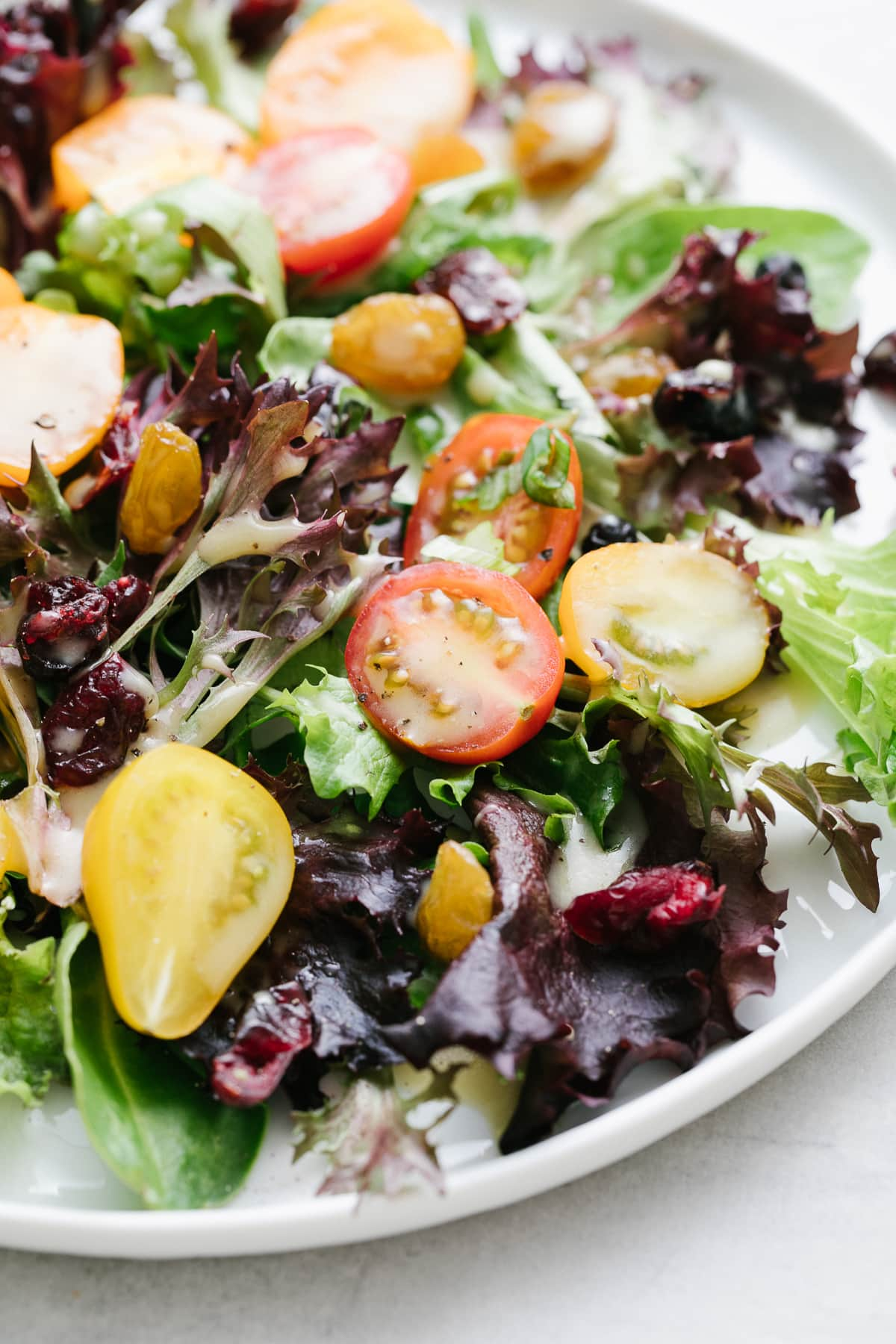 up close, side angle view of a salad with healthy maple dijon dressing with items surrounding.