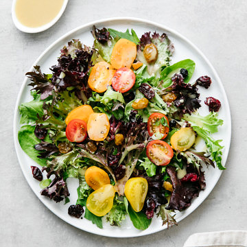 top down view of a salad with healthy maple dijon dressing with items surrounding.
