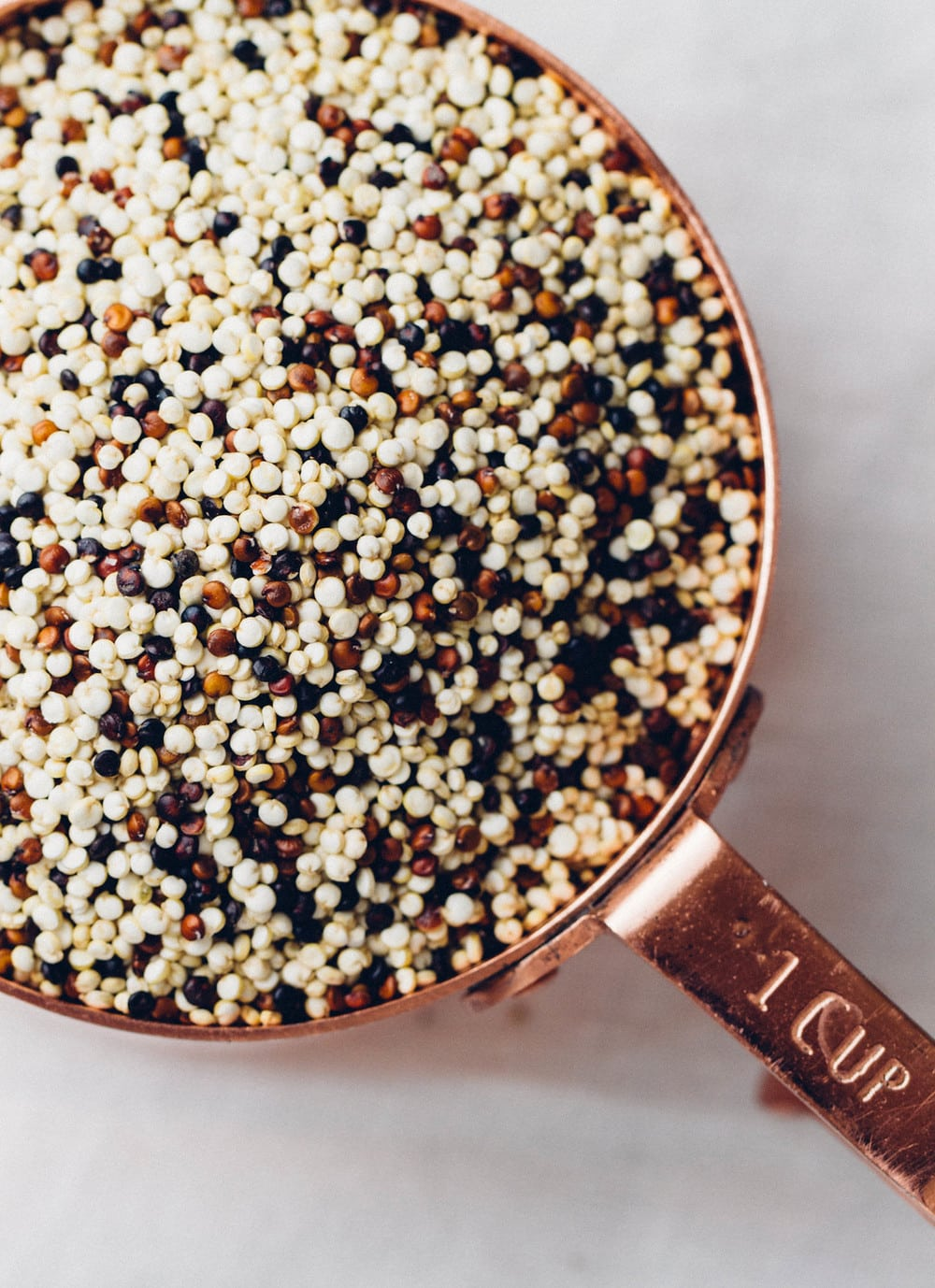 top down view of dried quinoa in a measuring cup