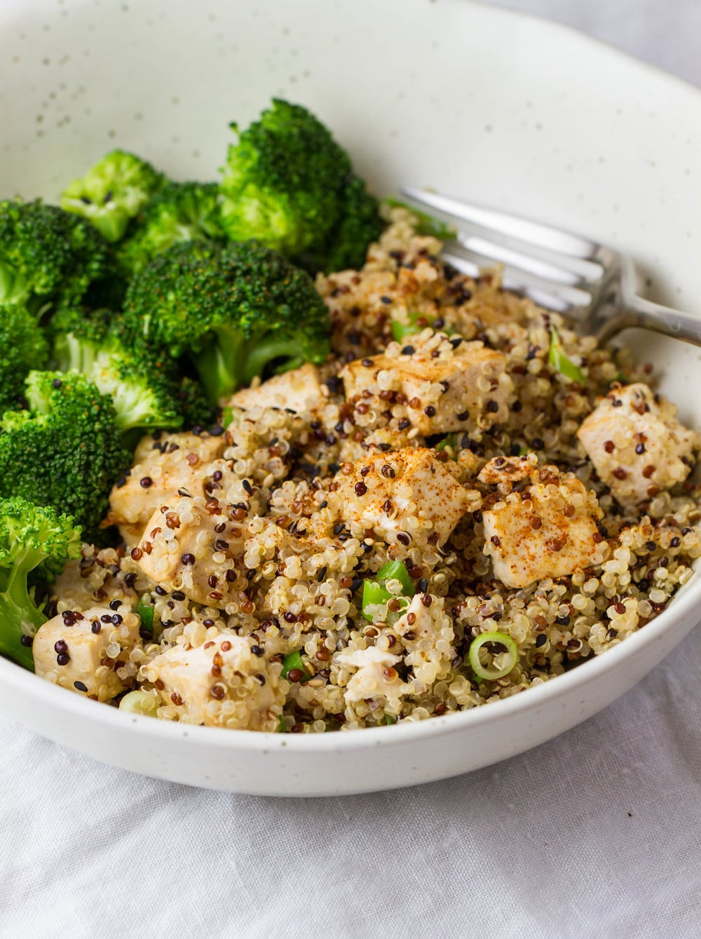 side angle view of sesame quinoa tofu with steamed broccoli in a bowl with fork