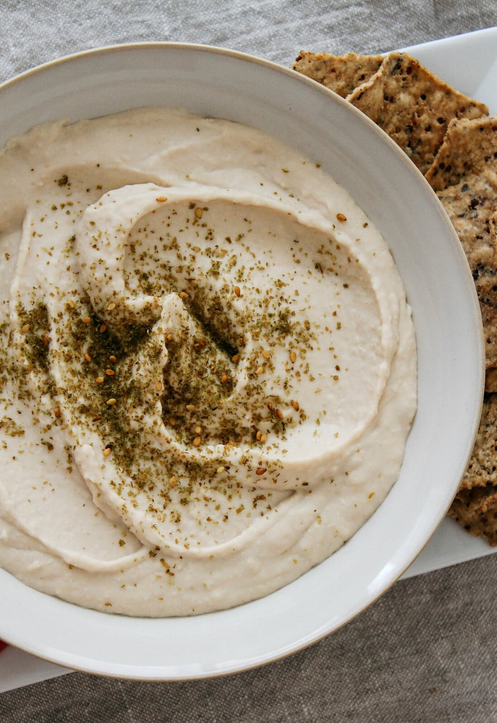 top down view of white bean hummus garnished with za'atar in a white bowl.