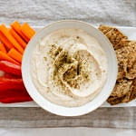 top down view of white bean hummus in a bowl with fresh veggies and chips for dipping on a plate.