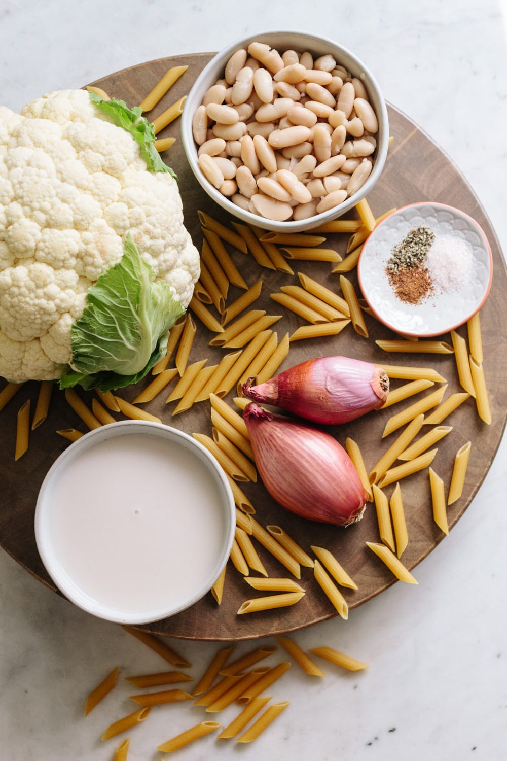 top down view of ingredients for white bean cauliflower alfredo sauce displayed on a round cutting board.