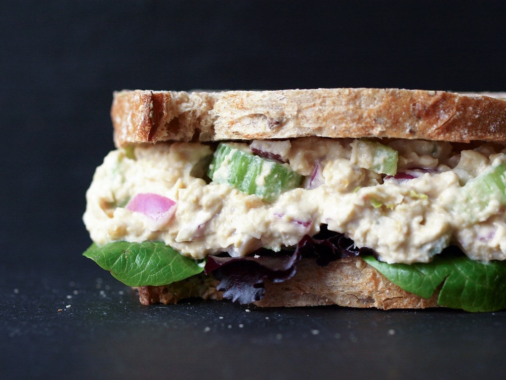 up close, head on shot of vegan chickpea tuna salad sandwich with leafy greens whole grain bread