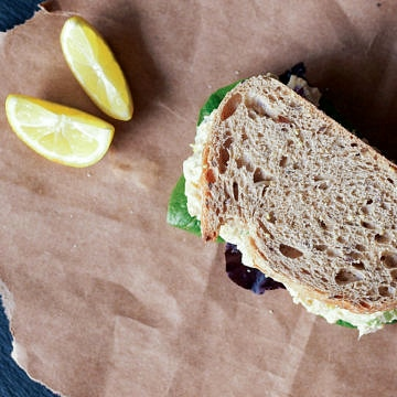 top down view of vegan chickpea tuna salad sandwich and lemon slices on a brown paper bag