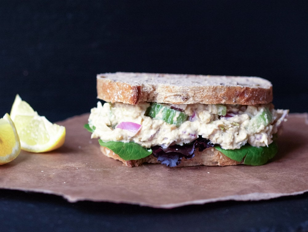 head on shot of vegan chickpea tuna salad sandwich with leafy greens and whole grain bread on a brown paper bag
