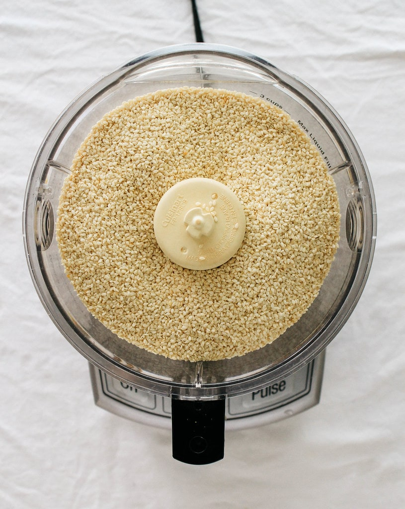 top down view of white sesame seeds added to the bowl of a food processor.