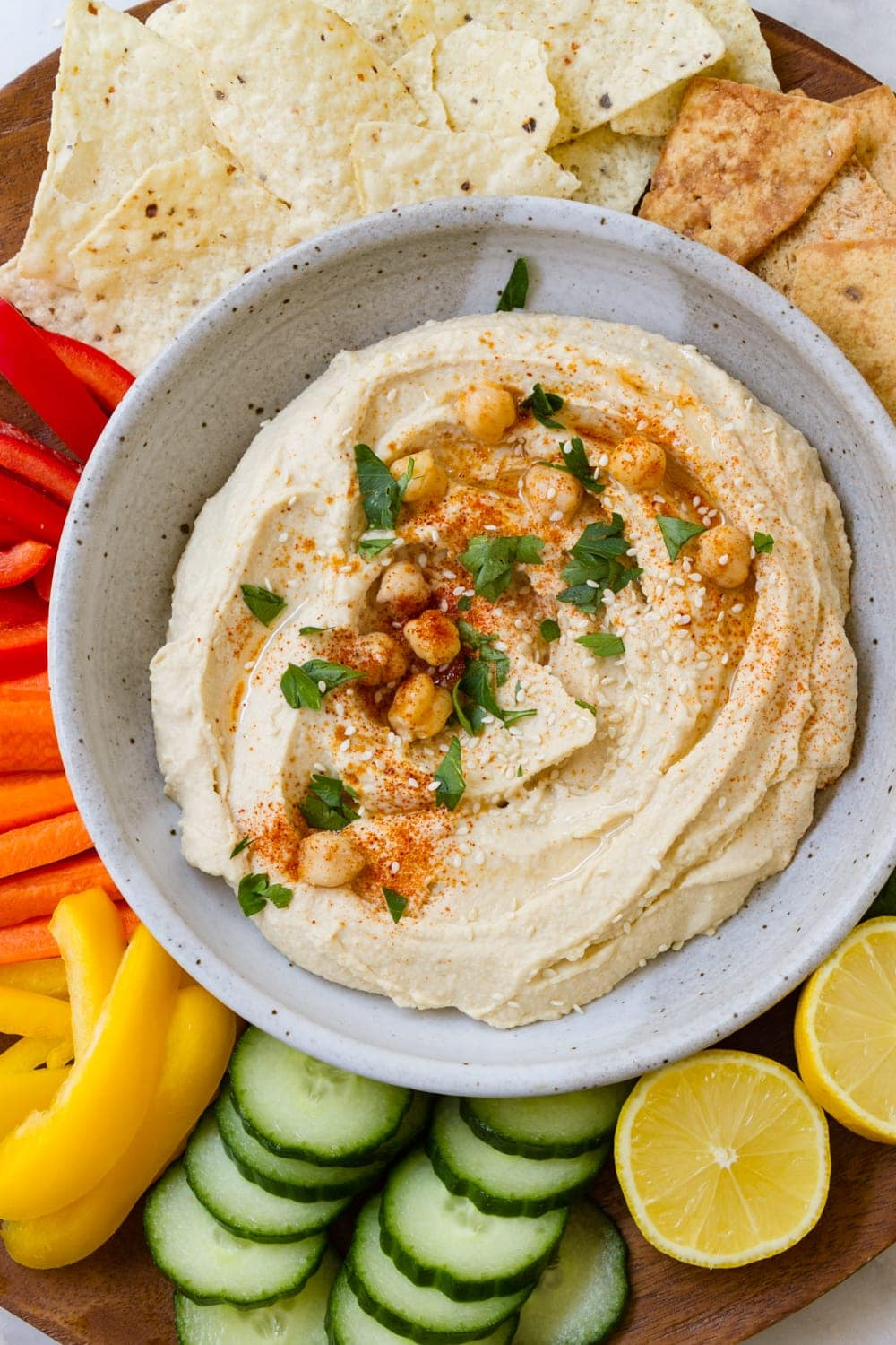 top down view of best authentic hummus in a bowl topped with parsley, chickpeas and paprika, and surrounded by chips and sliced vegetables for dipping.