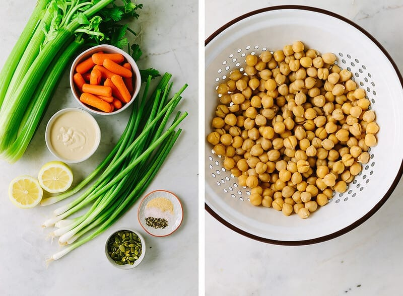 ingredients for mashed chickpea salad on a marble slab. Ingredients include carrots, chickpeas, celery, green onions, hummus, dijon, and pepitas