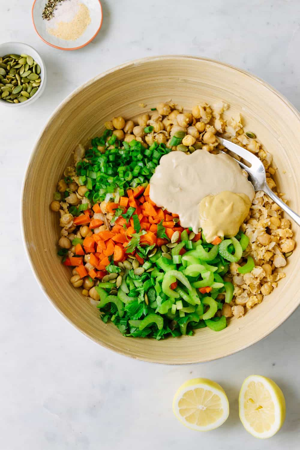 mashed chickpea salad being combined in a large serving bowl