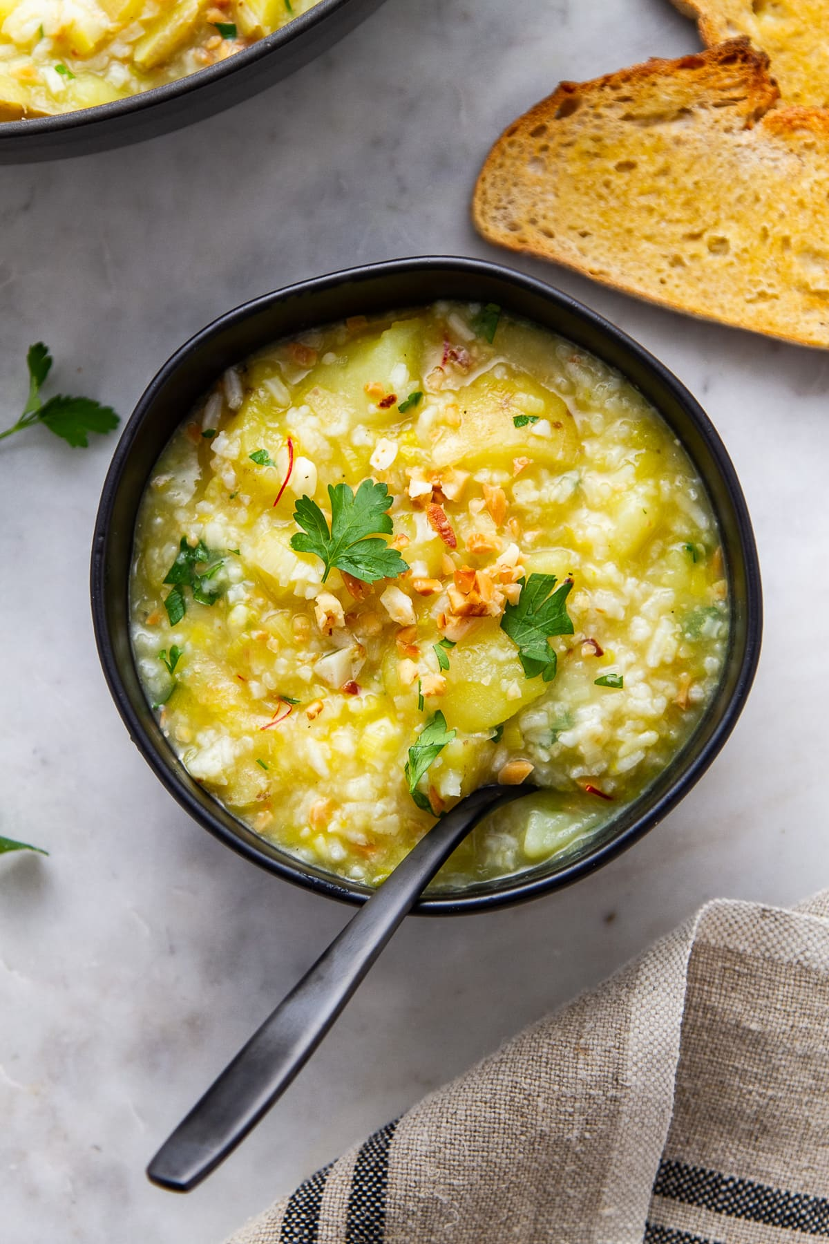 top down view of saffron potato leek soup in a bowl with spoon and items surrounded by items.